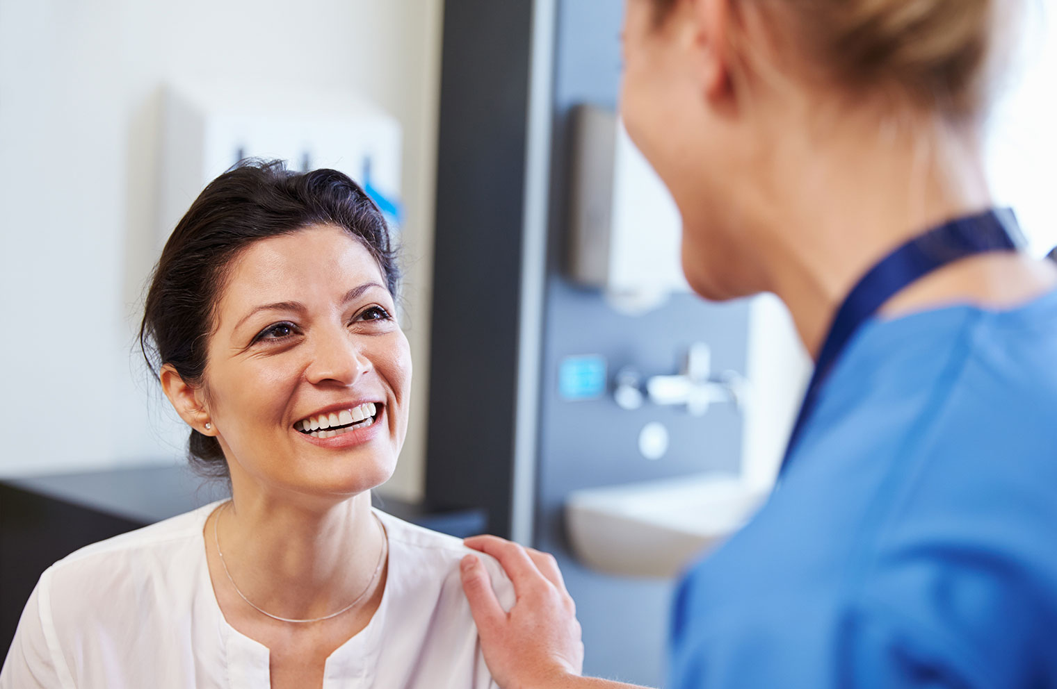 Image of woman smiling as she receives checkup from female doctor.