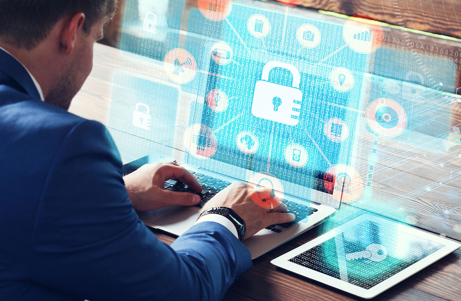 Image of padlock and security graphics overlaying image of man at desk with laptop