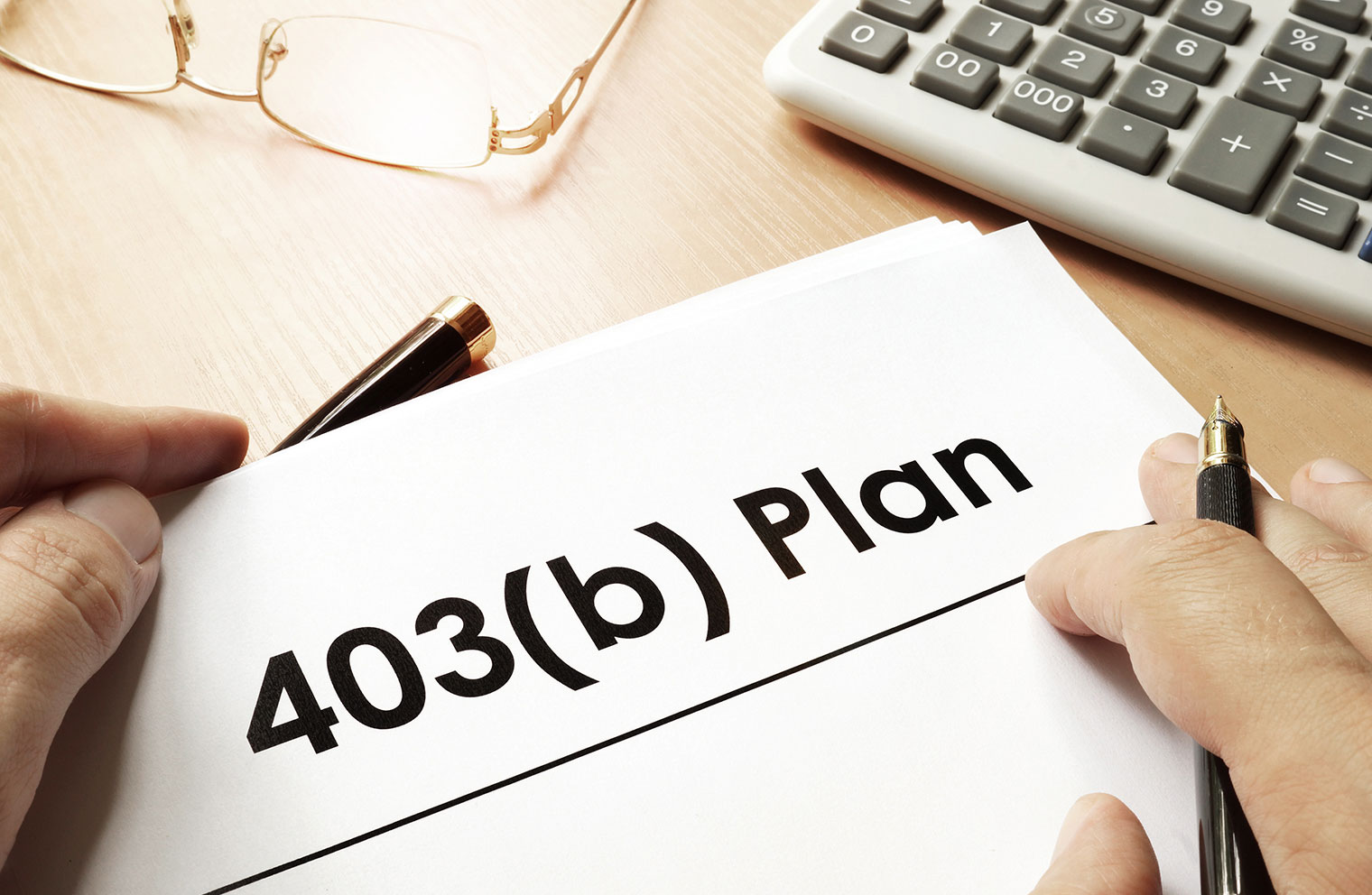 Image of 403(b) Plan written on paper at desk with calculator.