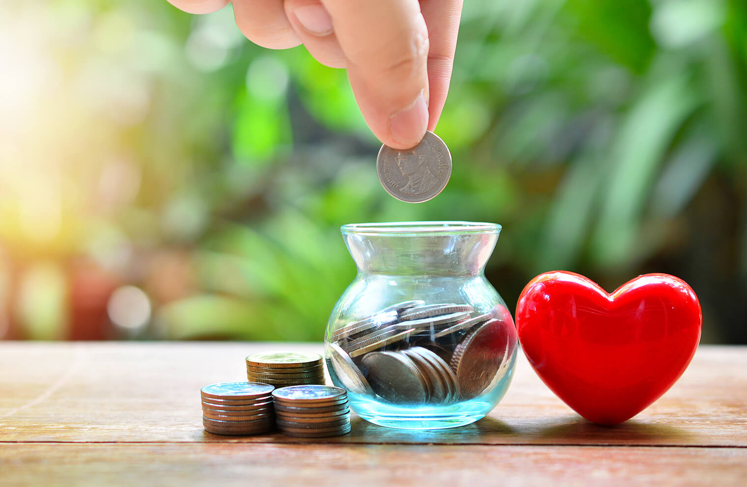Picture of a person's hand dropping quarters into a tiny glass vase that is next to more quarters to the left and a toy heart to the right.