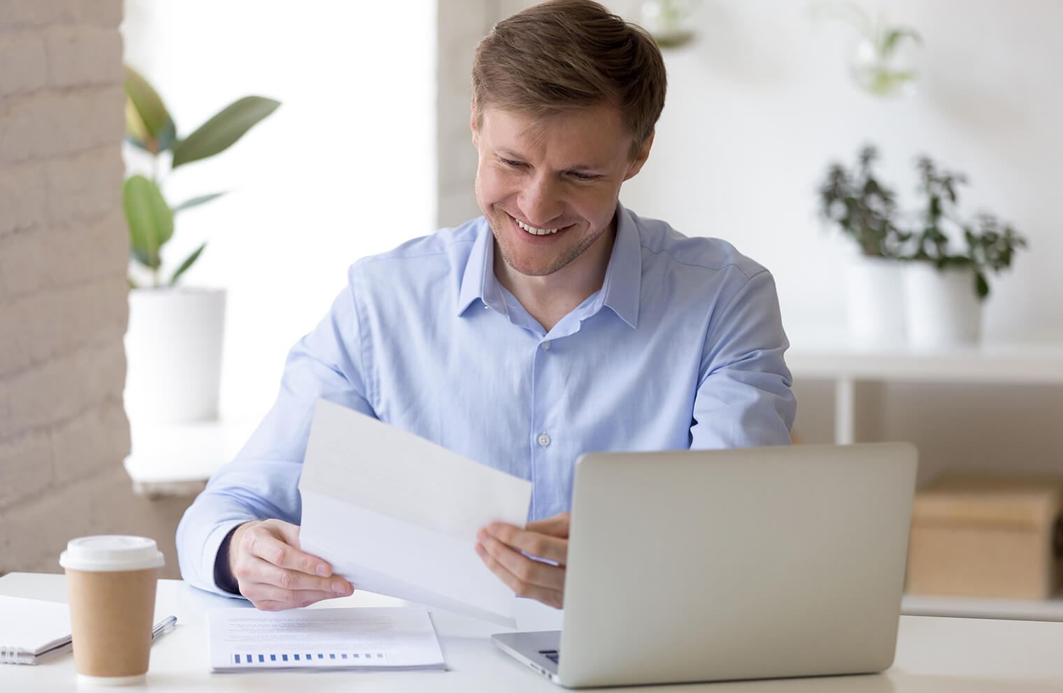 Picture of a man in a blue dress shirt, smiling and holding a piece of paper. He is sitting at  a white desk that has notebooks, coffee, documents, and a laptop on it.